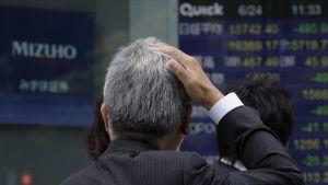 Pörssin työntekijä katsoo tauluja.
