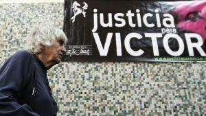 Vanhan naisen vieressä on juliste, jossa lukee oikeutta Victorille.