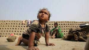Pikkulapsi konttaa hiekkamaalla. Taustalla istuu nainen, hänen takanaan tiiliä ladottuina kuivumaan.