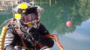 Ammattisukeltaja menossa veteen sukellusvarusteissa.