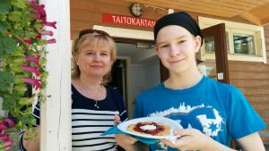 Pirjo Hämynen ja Santeri Heikkinen Taitokartanon kuistilla.