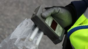 Poliisin kädessä alkometri ja puhallutuspillejä.
