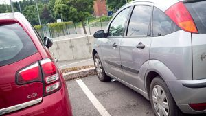 Punainen ja hopeanharmaa henkilöauto.