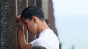 Mies itkee vasten Yhdysvaltojen ja Meksikon välistä raja-aitaa.