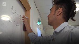 Mies kirjoittaa taululle
