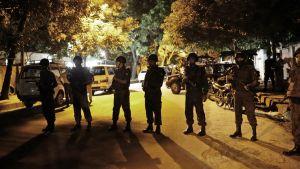 Aseistautuneita miehiä seisoo kadulla rivissä.