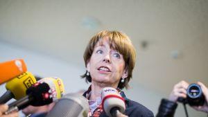 Naisen edessä useit mikrofoneja.