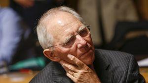 Wolfgang Schäuble nojaa vakavana poskeensa.