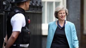 Hymyilevä Theresa May kulkee poliisin ohi.
