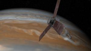 Piirroskuva litteästä luotaimesta, joka lähestyy aurinkopaneelit levällään paksujen pilvien peittämää Jupiteria.