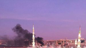Itsemurhapommittaja surmasi itsensä ja neljä vartijaa islamin toiseksi pyhimmässä kaupungissa Medinassa 4.7.2016. Isku tapahtui Profeetan moskeijan lähellä sijaitsevalla pysäköintialueella. Kuvassa moskeija, jonka takaa nousee musta savupatsas. Kuvan etualalla tuhannet ihmiset ovat saapuneet rukoilemaan.