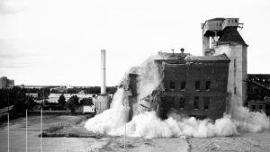 Mustavalkokuva Pietarsaaren UPM:n tehtaan räjäyttämisestä. Kuvassa tehdas romahtaa.