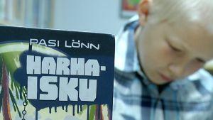 Kirjastossa lukeva poika.