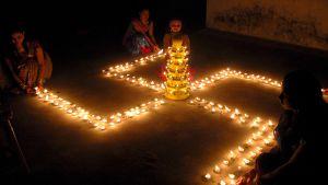 Naiset ovat muotoilleet kynttilöistä suuren hakaristin maahan. Hakaristin keskellä on torni, jossa on kynttilöitä.