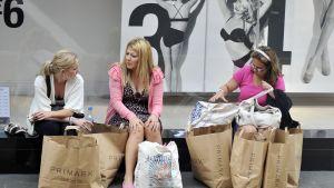 Naisia istuu ostoskeskuksen ulkopuolella ostoskassien kanssa.