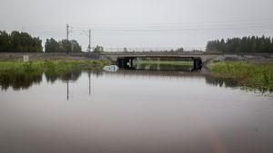 Sadevesi tulvii Klapurintien alikulussa Kälviällä ja peittää henkilöauton alleen.