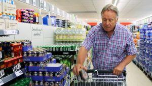 Mies laittaa oluttölkkejä ostoskärryyn.