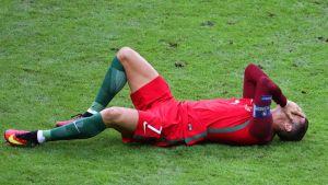 Portugalin Cristiano Ronaldo pitelee kasvojaan nurmen pinnassa.