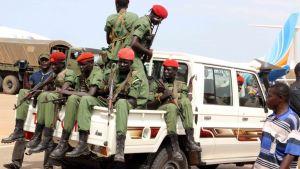 Univormupukuisia, punabaskerisia sotilaita aseineen avolava-autossa.