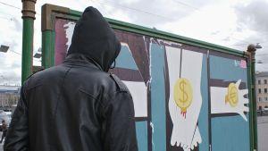 Mustaan huppariin pukeutunut mies seisoo julistemaisen katutaidetyön edessä.