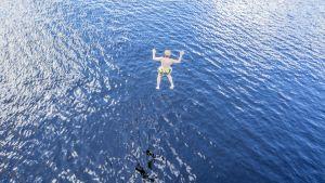 Poika hyppää veteen hyppytornista