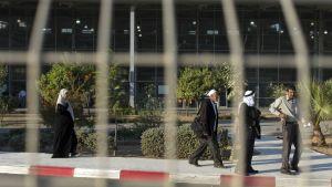 Kuva on otettu kaltereiden läpi. Huivipäinen nainen ja kolme miestä kävelevät rajanylityspaikan läpi.