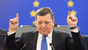 Barroso seisoo etusormet pystyssä. Hänen päänsä takana näkyy EU:n lipun ympyränmuotoinen tähtikuvio.