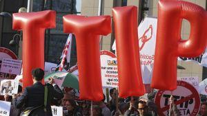 Kuvassa isot, punaiset ilmapallokirjaimet jotka muodostavat lyhenteen TTIP ja TTIP:tä vastustavia mielenosoittajia.