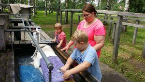 Taina Palo halusi opettaa lapsilleen perinteistä mattojen porstaamista. Elsa ja Onni olivatkin innokkaita apulaisia.