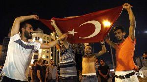 Turkin presidentin kannattajat huutavat iskulauseita Taksimin aukiolla Istanbulissa.