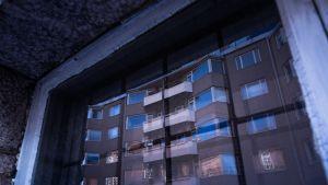 Ikkunassa heijastus kerrostalosta.