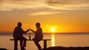 Vanhempi pariskunta nauttii viinistä ja toistensa seurasta.