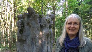 Nainen seisoo puistossa sijaitsevan suuren ihmisfiguureista koostuvan veistoksen edessä.