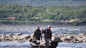 Kaksi miestä joella.