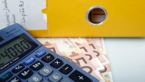 Laskukone, seteleitä ja keltainen kansio.