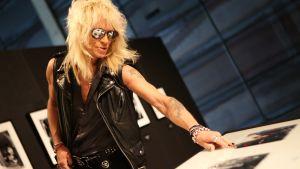 Rock-tähti Michael Monroe katselee Hanoi Rocks -yhtyeen valokuvia.