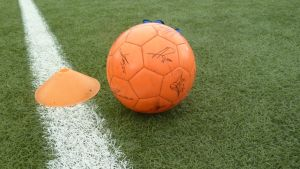 Nimikirjoituksilla varustettu jalkapallo tekonurmella.