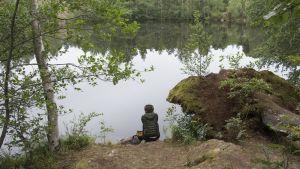 Polly Stanton istuu lammen rannalla.