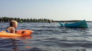 Lapset uimapatjoilla vedessä.
