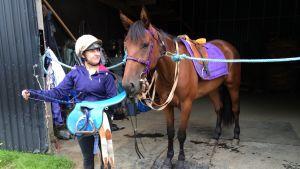 Monte-ratsastaja Sanna Riikonen esittelee kevyttä montesatulaa hevosensa vierellä.