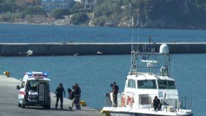 Laaja kuva, jossa joukko miehiä kantaa ruumissäkkiä veneestä ambulanssiin.