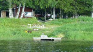 Kesämökki joen rannassa.
