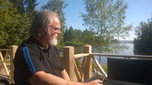 Jorma Aspegren istuu saunamökin kuistilla, taustalla merimaisemaa.