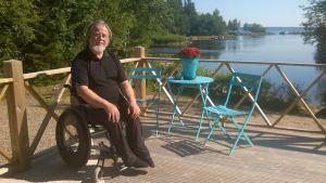 Jorma Aspegren istuu mökkisaunan kuistilla, taustalla merimaisemaa.