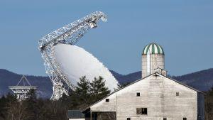 Valtava radioteleskooppi suuren navetan takana.