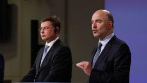 EU:n talouskomissaari Pierre Moscovici (oik.) ja EU-komission varapuheenjohtaja Valdis Dombrovskis tiedotustilaisuudessa 27. heinäkuuta.