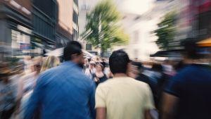 Ihmiset kävelevät kaupungin vilinässä ja tungoksessa.