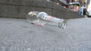 Tyhjä pullo kävelykadulla.
