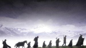 Joukko vaeltaa sumuisessa nummimaisemassa.