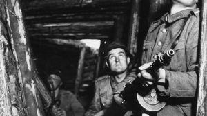 """Jatkosota. Neuvostoliiton suurhyökkäys. Kolme suomalaista sotilasta asemissa korsun ovella, yhdellä sotilaalla kädessään Suomi-konepistooli. Sotilaita. """"Jermuja, jermu""""."""